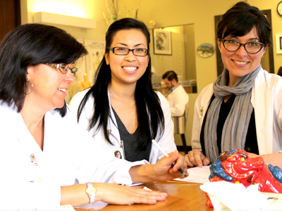 Michelle Medina (right) poses with students at the Acupuncture & Integrative Medicine College (AIMC) in Berkeley.