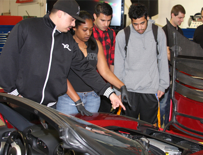 Chabot College students Emanuel Ruiz, Jessica Hollie, Faizan Fedaie, and Theron Reyes look under the hood of an electric Tesla roadster during Tesla Motors' visit to the college's Hybrid Auto Technology class. Students will be pursuing technical careers related to the newest hybrid and electric cars.