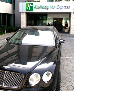 Bentley sedan parked in front of the Holiday Inn Express hotel in Portugal.